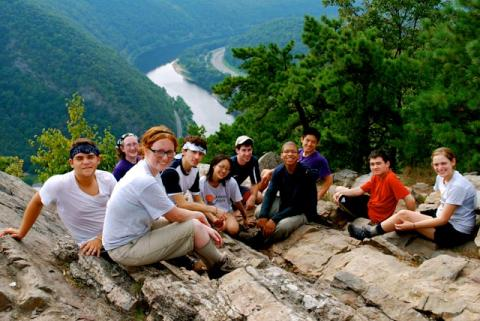 Group of people sitting at top of Mount Tammany with river visible in background